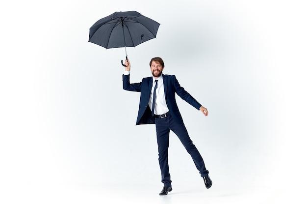 Mężczyzna w garniturze trzymający parasol w dłoniach elegancki styl pogoda deszcz