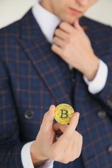 Mężczyzna w garniturze trzymający złotego bitcoina - symbol międzynarodowej wirtualnej kryptowaluty. na białym tle.