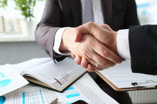 Mężczyzna w garniturze uścisnąć dłoń jak cześć w biurze