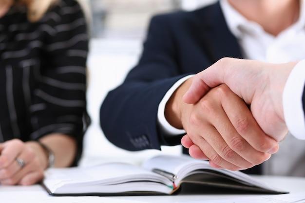 Mężczyzna w garniturze uścisnąć dłoń jako cześć w biurze zbliżenie