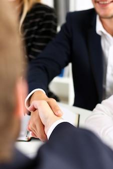 Mężczyzna w garniturze uścisnąć dłoń jako cześć w biurze