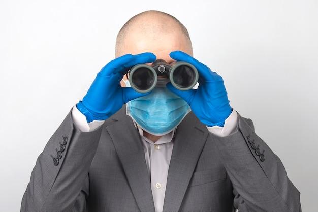 Mężczyzna w garniturze, w masce medycznej i rękawiczkach ochronnych patrzy przez lornetkę. cele w odnoszącym sukcesy biznesie z problemami kwarantanny podczas epidemii koronawirusa.