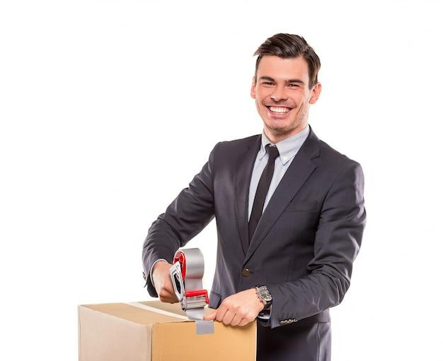 Mężczyzna w garniturze, wbija pudełko i uśmiecha się.