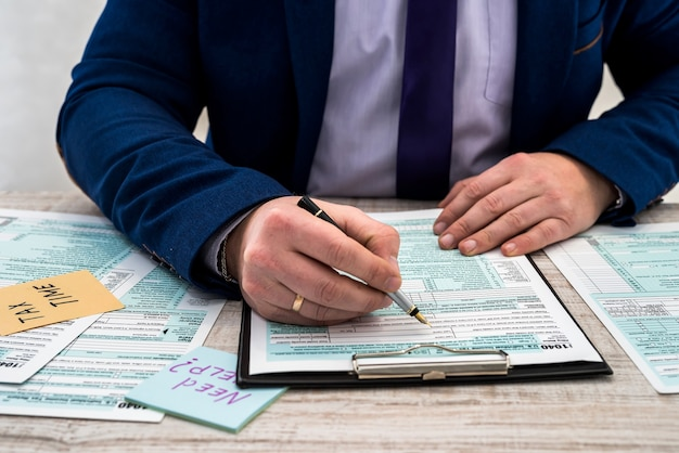 Mężczyzna W Garniturze Wypełnia Formularz Podatkowy 1040 W Usa. Czas Podatkowy. Koncepcja Rachunkowości Premium Zdjęcia