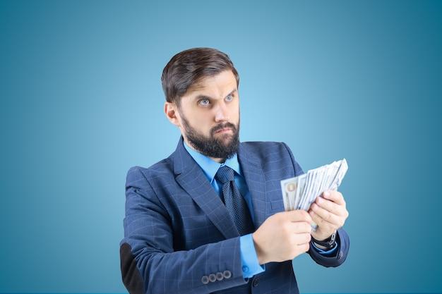 Mężczyzna w garniturze z banknotami w rękach, myślący o finansach, odwraca wzrok