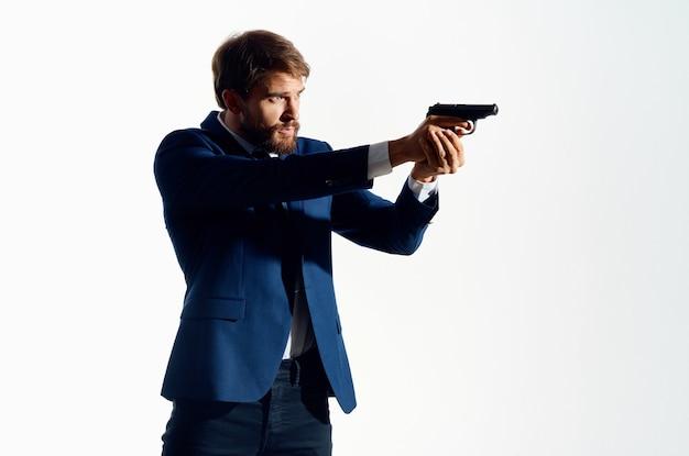 Mężczyzna w garniturze z bronią w ręku przestroga detektywa.