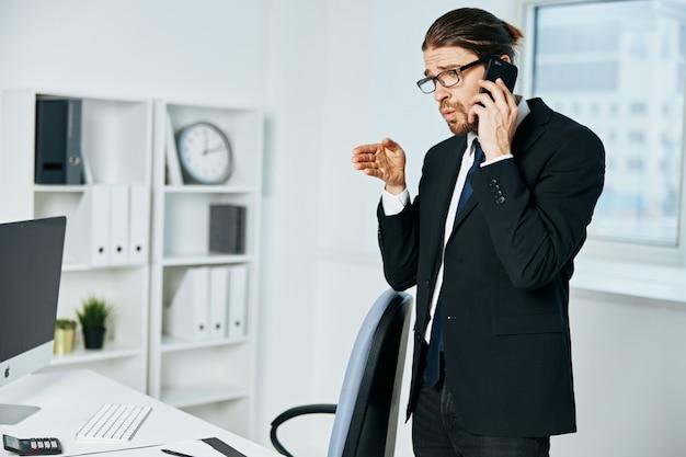Mężczyzna w garniturze z dokumentami w komunikacji przez telefon kierownika