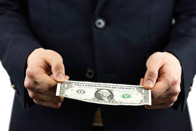 Mężczyzna w garniturze z dolarem w dłoni.