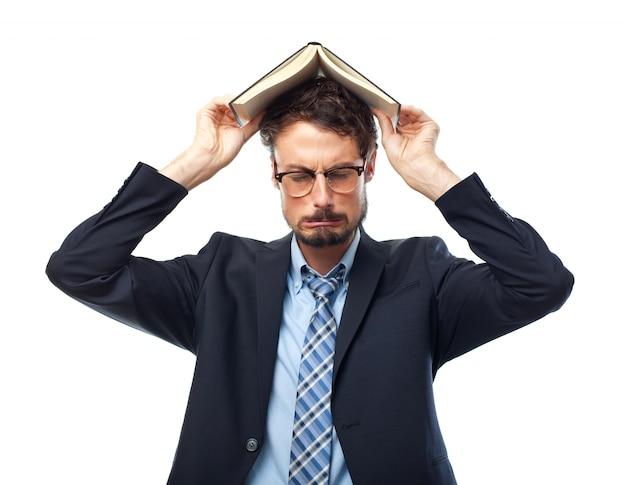 Mężczyzna w garniturze z książką na głowie