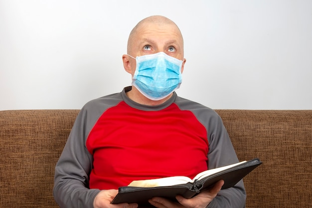 Mężczyzna w garniturze z maską medyczną na twarzy studiuje biblię.