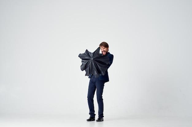 Mężczyzna w garniturze z parasolem chroniącym emocje przed deszczem