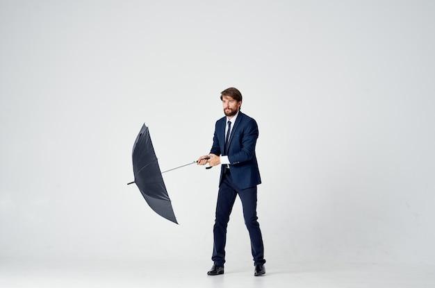 Mężczyzna w garniturze z parasolem chroniącym przed deszczem