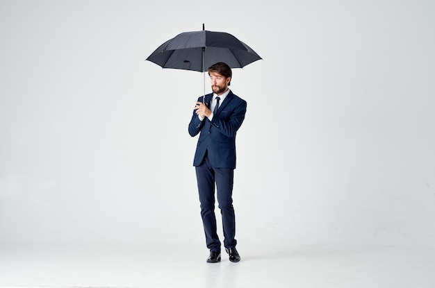 Mężczyzna w garniturze z parasolem w rękach ochrona przed warunkami pogodowymi