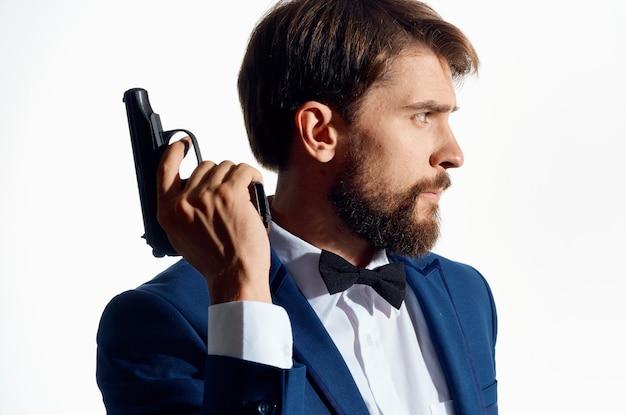 Mężczyzna w garniturze z pistoletem w dłoni jasnym tle