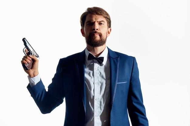 Mężczyzna w garniturze z pistoletem w ręku studyjne emocje