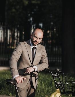 Mężczyzna w garniturze z rowerem. ekologiczny transport i zdrowy, aktywny tryb życia. biznesmen jedzie na rowerze do pracy