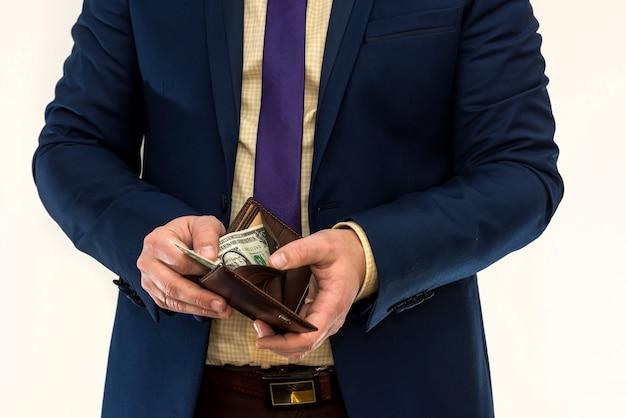 Mężczyzna w garniturze zagląda do portfela i wyciąga tylko 1