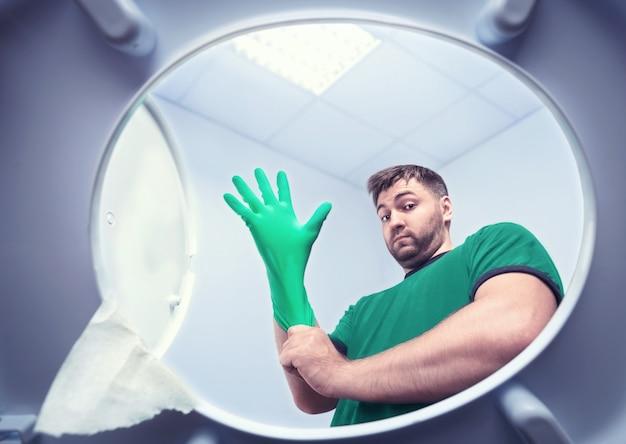 Mężczyzna w gumowej rękawicy w toalecie