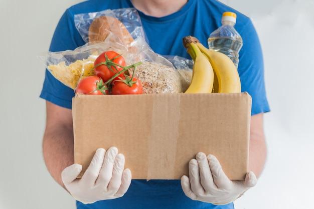 Mężczyzna w gumowych rękawiczkach, trzymając pudełko z jedzeniem