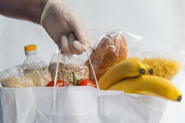 Mężczyzna w gumowych rękawiczkach trzymający papierową torbę z jedzeniem