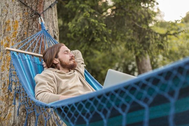Mężczyzna w hamaku cieszy się naturę z laptopem