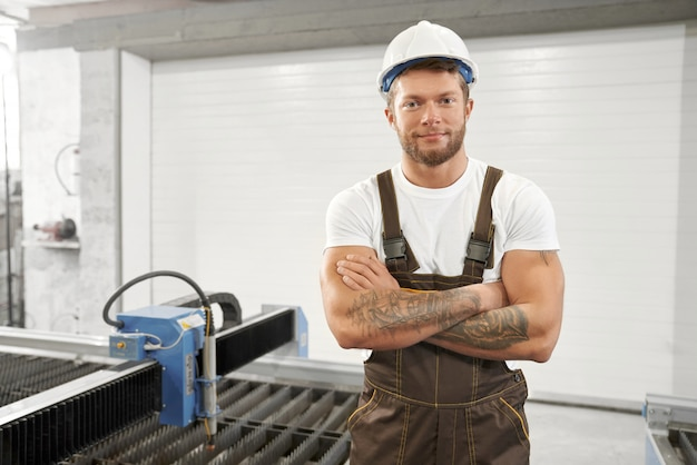 Mężczyzna w hełm pozyci z fałdowymi rękami na fabryce