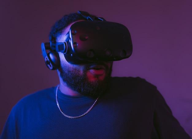 Mężczyzna w hełmie cyber. nowe gry vr w neonowym pokoju