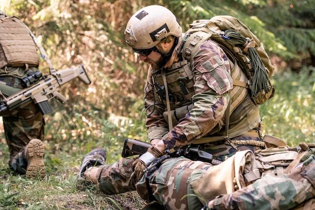 Mężczyzna w hełmie i okularach przeciwsłonecznych badający nogę rannego żołnierza na polu bitwy