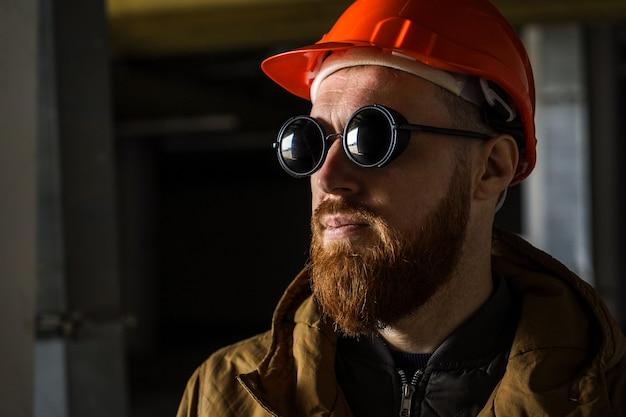 Mężczyzna w hełmie i okulary przeciwsłoneczne w ciemnym pokoju, odwraca wzrok