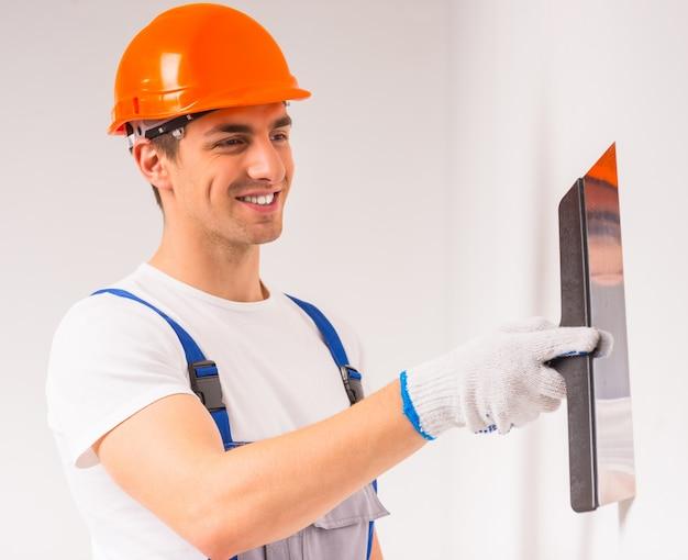 Mężczyzna w hełmie maluje ścianę i uśmiecha się.