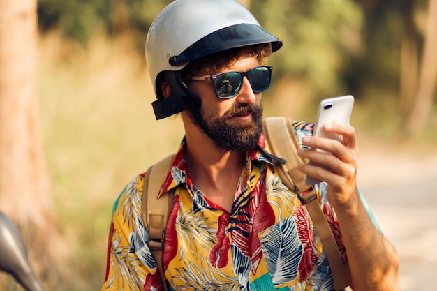 Mężczyzna w hełmie siedzi na motocyklu i przy użyciu telefonu komórkowego