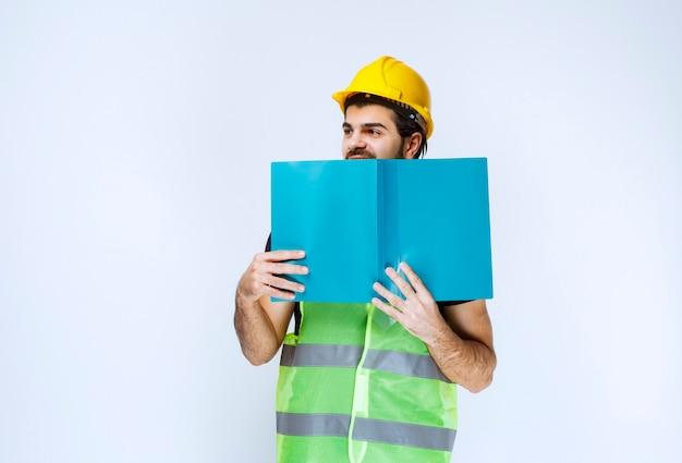 Mężczyzna w hełmie, trzymający przy twarzy niebieską teczkę.