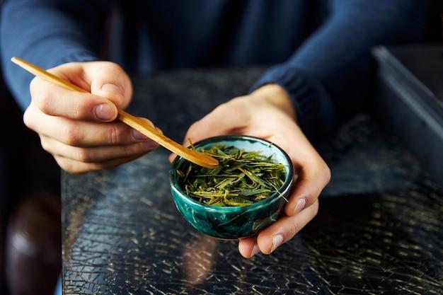 Mężczyzna w jego rękach pokazuje spawanie zielonej herbaty