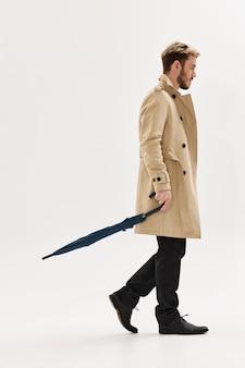Mężczyzna w jesiennym beżowym płaszczu z parasolką w dłoniach chroni przed deszczem w nowoczesnym stylu