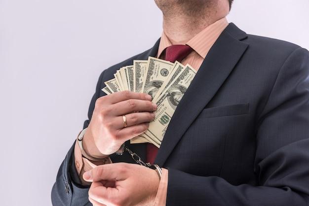Mężczyzna w kajdankach trzymając banknotów dolara na białym tle, z bliska. aresztować