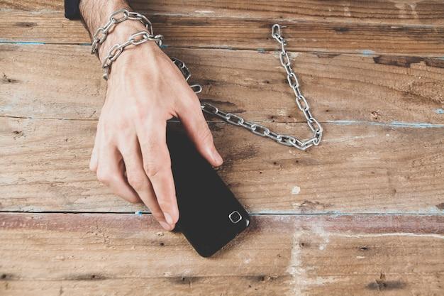 Mężczyzna w kajdankach trzymający telefon