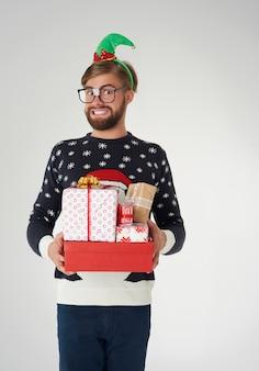 Mężczyzna w kapeluszu elfa i wiele prezentów świątecznych