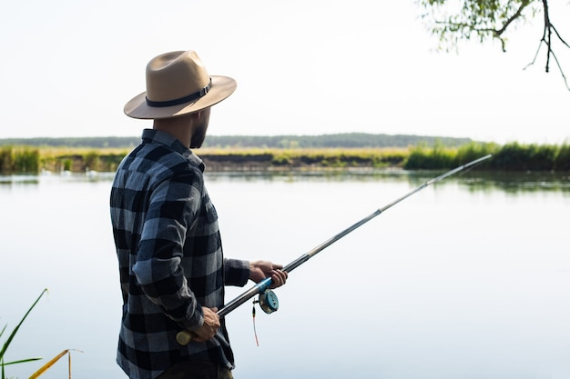 Mężczyzna w kapeluszu i koszuli w kratę łowi ryby na linie nad rzeką.