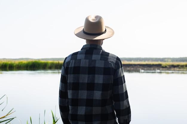 Mężczyzna w kapeluszu i koszuli w kratę podziwia krajobraz nad rzeką.