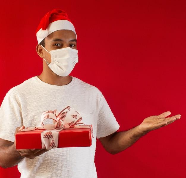 Mężczyzna w kapeluszu i na sobie maskę z prezentem w dłoniach