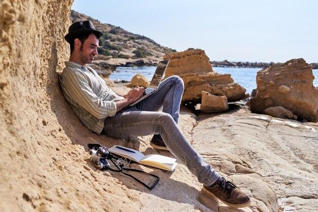 Mężczyzna w kapeluszu korzystający z klawiatury laptopa na egzotycznej plaży z aparatem i notatnikiem