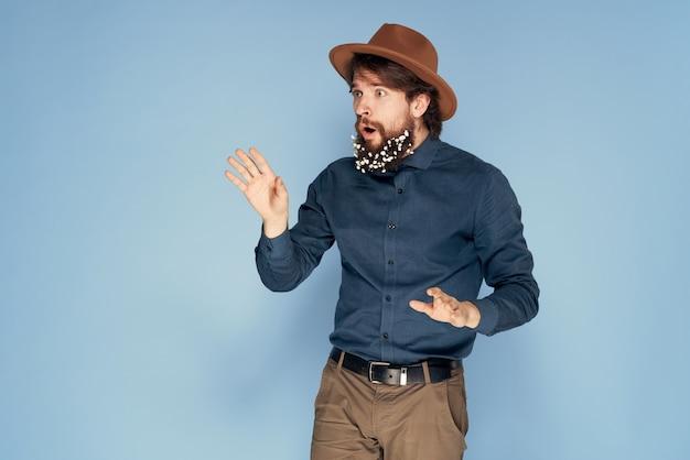 Mężczyzna w kapeluszu kwiaty w brodę ekologia styl emocje niebieskie tło. wysokiej jakości zdjęcie