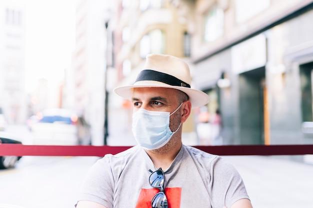 Mężczyzna w kapeluszu na ulicy nosi maskę