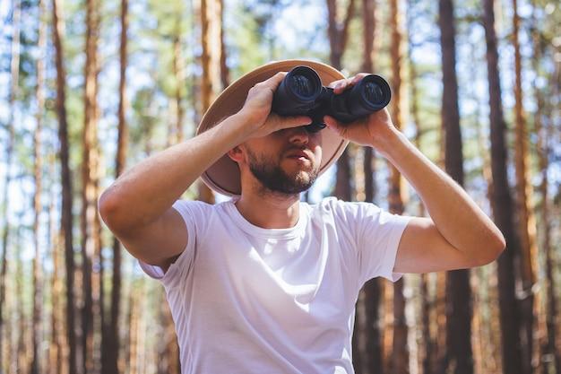 Mężczyzna w kapeluszu patrzy przez lornetkę podczas wyprawy na kemping. wycieczka w góry, las.