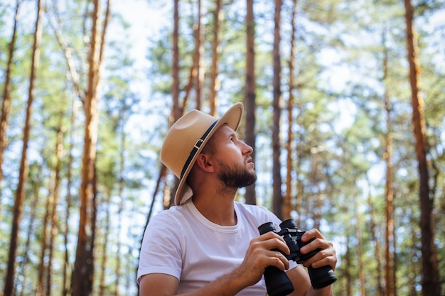Mężczyzna w kapeluszu trzyma lornetkę podczas wyprawy na kemping. wycieczka w góry, las.