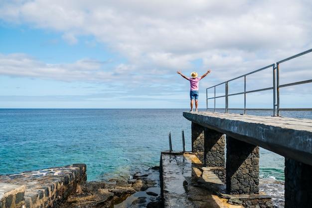Mężczyzna w kapeluszu, turysta, latem, cieszy się widokiem na morze z kamiennego spaceru po wybrzeżu