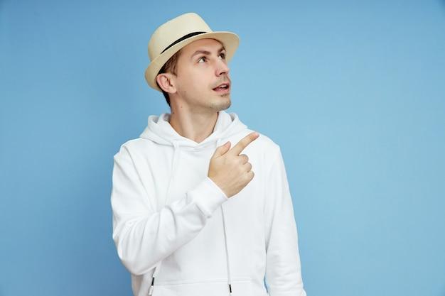 Mężczyzna w kapeluszu uśmiecha się i wskazuje w górę