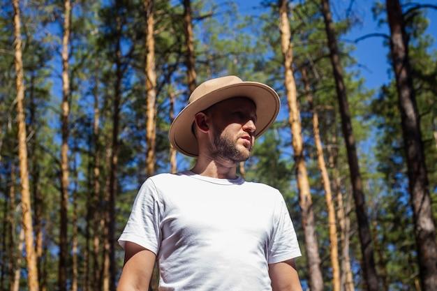 Mężczyzna w kapeluszu w lesie. wycieczka w góry, las.