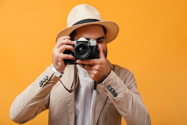 Mężczyzna w kapeluszu z szerokim rondem robi zdjęcie aparatem retro