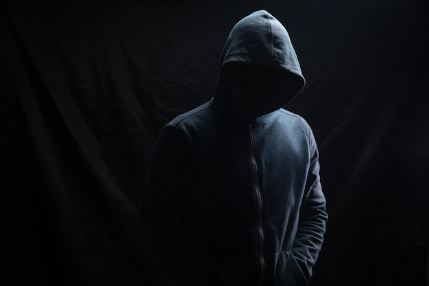 Mężczyzna w kapturze stoi na czarnym tle